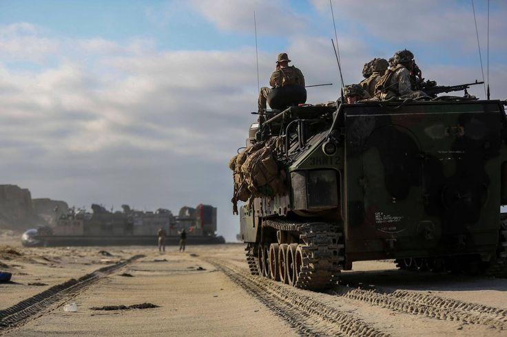 Marines come ashore in armored assault vehicles after disembarking from the landing craft