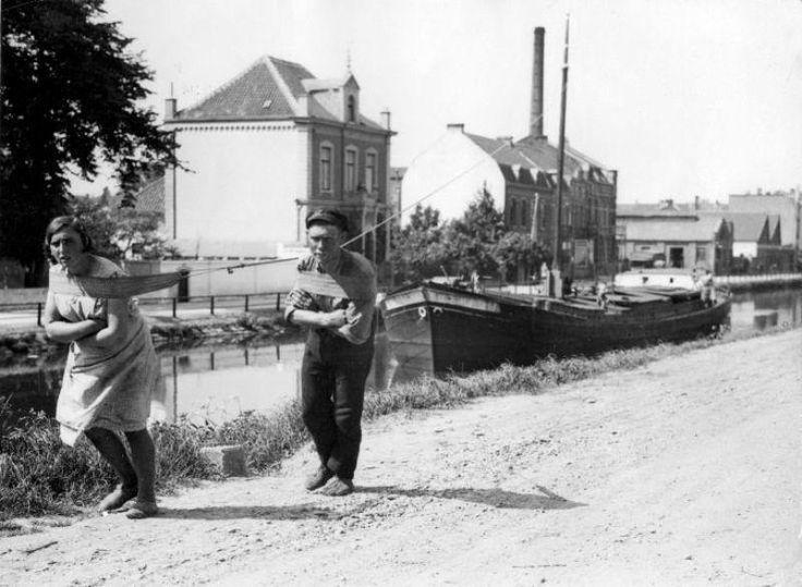 Trekschuit jager. Man en vrouw trekken een vrachtschip door een binnenkanaal. Plaats onbekend, 27 mei 1931