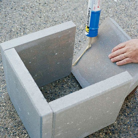 DIY plant boxes with a modern look are easy and inexpensive to make with square concrete pavers and adhesive.