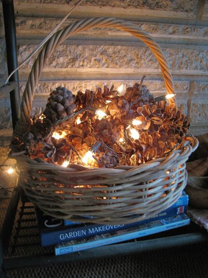 If you dream of reading in front of a fire, but are without a fireplace, this is an inviting alternative for snowy winter evenings... fill a vintage basket with pine cones and drape a string or two of battery-operated miniature lights in and among the cones. With your nose in a book, you'll hardly notice the difference. Peace and Joy.