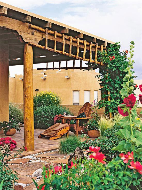The color, materials, and detailing of an outdoor structure should match the home and landscape. Here, a ramada, or covered porch, features round log posts teamed up with rough-sawn timbers that naturally accent the adobe structure nearby. A creative and authentic touch is the Native American ladder that supports climbing vines./