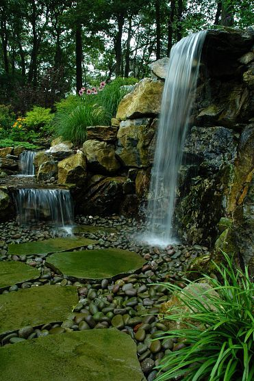 Bluestone stepping stone lead through the 7' natural waterfall and stream. Project by Deck and Patio Company Huntington Station New York. Read more- http://www.deckandpatio.com/DP_Blog/?p=1013