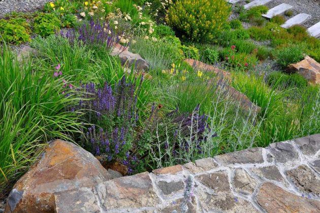 Prudký svah vedle zahradního domku je ztvárněn jako kamenná kaskáda, po které se dá snadno vystoupat, případně posedět mezi bylinkami
