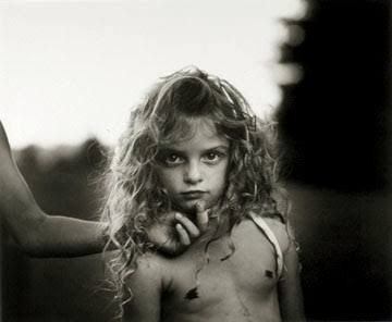Sally Mann: I like the way this image has been composed. The subject is centered in the frame  while this mysterious arm reaches in from the left side of the frame. I think the element of the arm directing the childs face adds to the overall photograph and creates a stronger image.