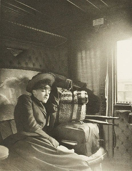 A woman who looks to be asleep on a train, 1895.