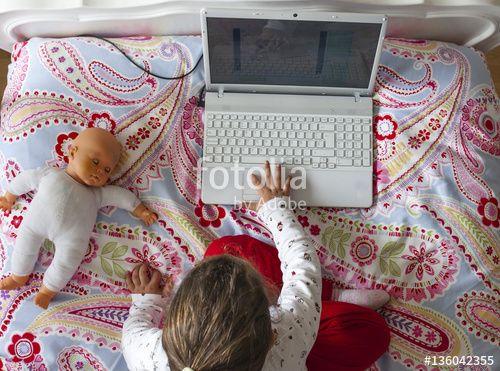 """Descargue la foto libre de derechos """"Little girl sitting in bed and playing online games"""" creada por juan_aunion al precio más bajo en Fotolia.com. Explore nuestro económico banco de imágenes para encontrar la foto perfecta para sus proyectos de marketing."""