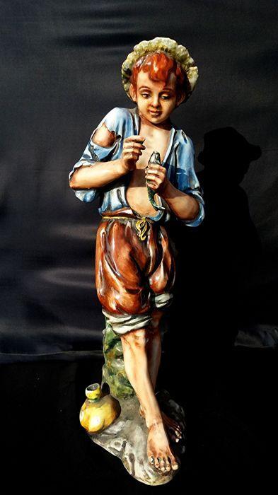 """A. Ciolli - Ragazzo con Pesce - 51 cm  Keramische sculptuur van een jonge man - polychroom geëmailleerd """"Majolica"""" van Italiaanse oorsprong die teruggaat tot circa 1950. Standbeeld van een jongen met vis gevangen in de hand gescheurd shirt korte broek gehouden door een tekenreeks met blote voeten rechterkant gele tas te verzamelen van de vangst ronde hoed op zijn hoofd met haar knippen met pony aan de voorkant; geschilderde polychroom kleuren met name licht blauw bruin geel en groen…"""