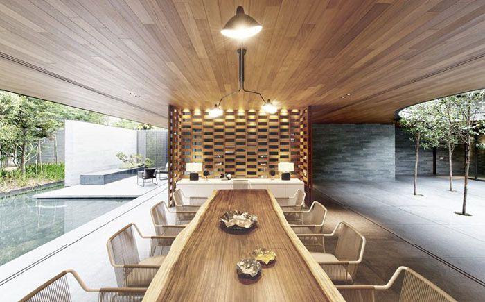 Кухня является частью открытой планировки. Она расположена вдоль стены сразу же за зоной гостиной. Длинный кухонный остров поражает своими размерами, превращаясь в обеденный стол и бар одновременно. С двух сторон стоят садовые кресла.