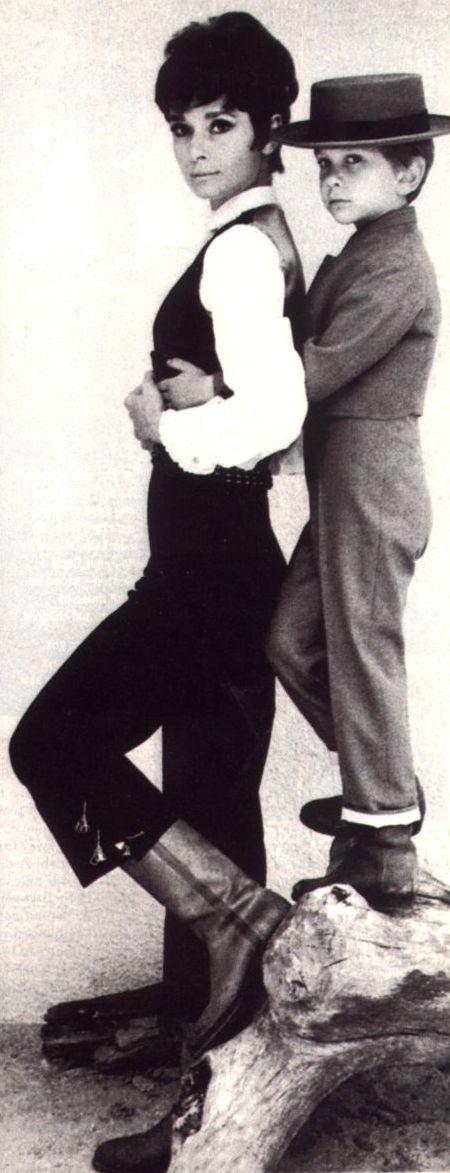 """Audrey Hepburn fotografiado con su hijo Sean Ferrer por Henry Clarke en París (Francia), en junio de 1965. -Audrey llevaba un """"traje corto"""" (en el mejor estilo """"torero"""") creado en exclusiva para ella por Givenchy (de """"La Feria de Sevilla"""", en español: """"Feria de abril de Sevilla"""", el desfile anual que se celebra en Sevilla, en abril 1965) y Hermès botas. Nota: El peinado de Audrey (llamado """"Coupe Infante '66"""") fue creado y realizado por Alexandre de París."""