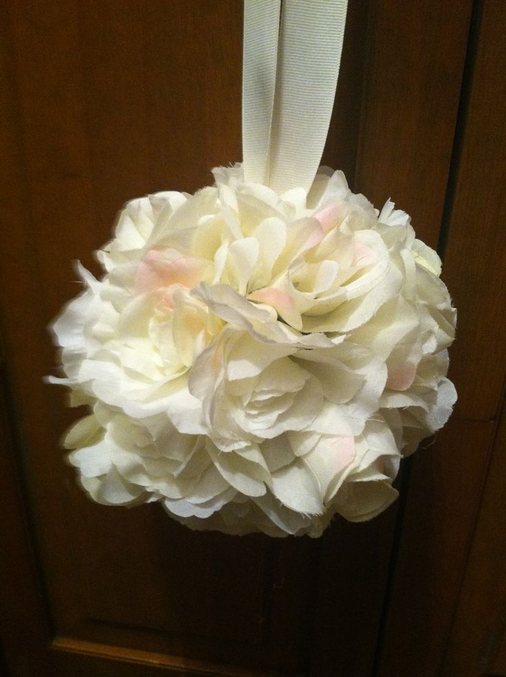 Flower ball for pews.  I used whiffle balls from dollar tree. Also used ivory, white and ivory flowers with hints of blush. Bought ribbon from Walmart. Ivory, textured. First, i pilled the ribbon through two holes. Then, Took off stems and hot glued the flowers to the holes of the whiffle ball.  Costs about 7 dollars each.