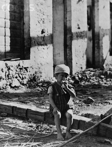 Small Boy Sits Among the Ruins of His Home, Greece - HU029312 - Rights Managed - Stock Photo - Corbis