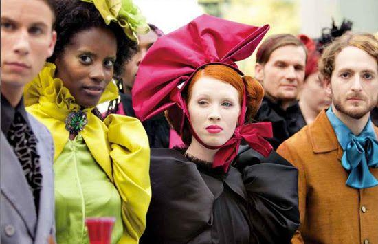 """Para los trajes de los personajes de la Capital, donde se supone que viven en absoluta riqueza, quiso crear trajes caros, ostentosos, con mucho colorido, pero a su vez con bastante abundancia de negro y rojo, ya que es gente que se """"divierte"""" viendo un concurso donde niños luchan por sobrevivir, matandose entre ellos. El vestuario de Effie Trinket, es sin duda de lo mas característico y llamativo."""