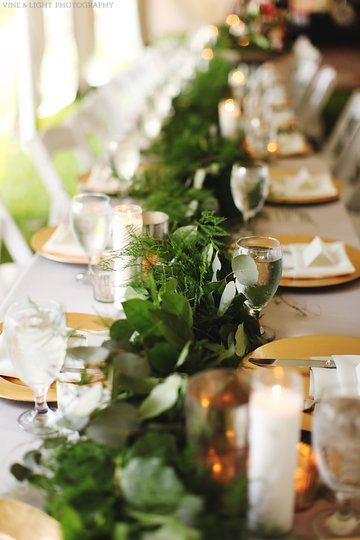 the farm style head table features a mix of greenery, candlelight and different metals. a garland of lemon leaf and plumosus fern is  highlighted by the glow of  mercury glass votives and cylinders, tall clear jar candles and gold chargers.