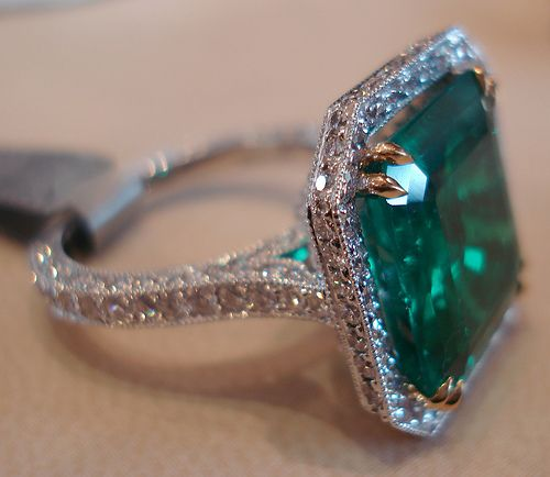 Colombian emerald ring.This particular stone is set in a white gold ring (except the claws in yellow gold) encased with small diamonds so as not to take away from the beauty of the stone itself. Note the selective focus on the claw grasping the stone. This emerald was mined in Colombia and with this setting costs the same as the average house price in London., UK
