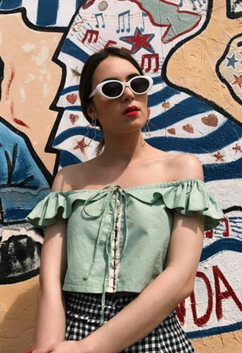 Could this look get any cooler? Probs not. Go for that retro-movie-star thing with a top that ticks all the sunny-life boxes… off-the-shoulder, ruffled and with a cutesy tie front. Finish with a check monochrome mini, white 60s-style sunnies and some tomato-red lippie. Add a mojito and you're more than good