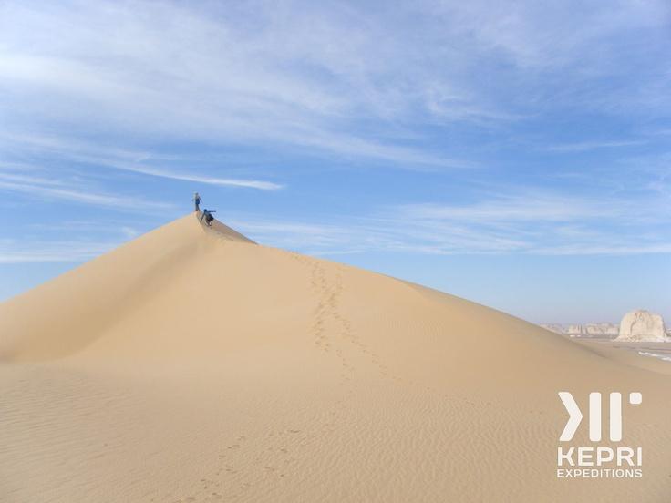 Some Kepri travelers climbing up a sand dune in the Sahara Desert, Egypt...