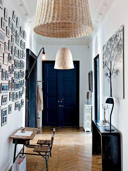 une grand entrée avec une décoration soignée : une porte d'entrée peinte en noir, un mur rempli de photos sous cadres, des grands abat-jours en osier