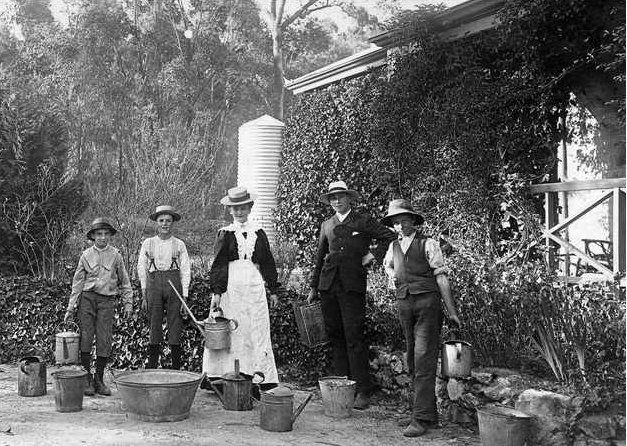 A woman carrying a watering can standing outside a house with four young male helpers, South Australia, 1910 - They carry a selection of buckets and cans to use for hand watering plants.