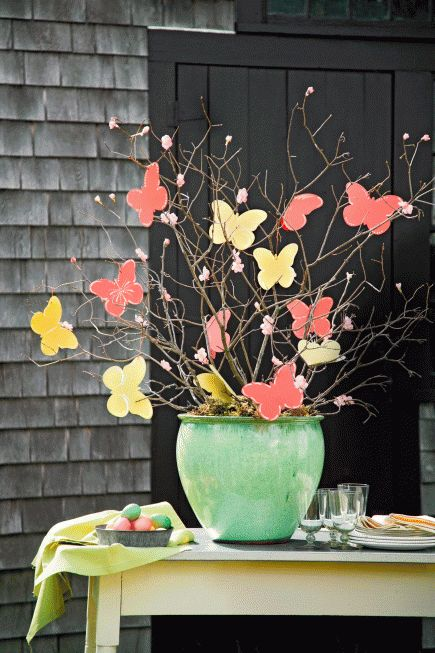 Cutouts of bold butterflies alight on branches in a spring-color vase. We hot-glued on the butterflies and paper blossoms. This bold look anchors a buffet table but would brighten any corner of a home.