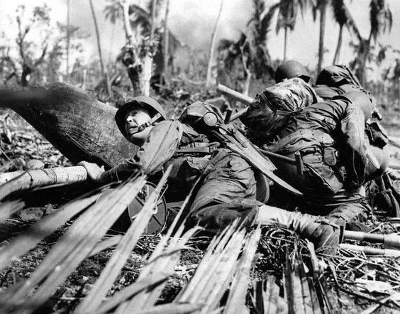 American soldiers take cover from fire of a Japanese machine gun in the Philippines during World War II (November 1944). The troops are part of the first wave to land on Leyte Island in the Philippine invasion.