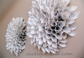 """The base was a 10"""" in diameter circle cut out of a cardboard box. She glued white poster board on it just in case the board peeks through.Then she rolled lots of paper cones and hot glued them on, starting from the outside.  A good pic of the process is shown on the original website."""