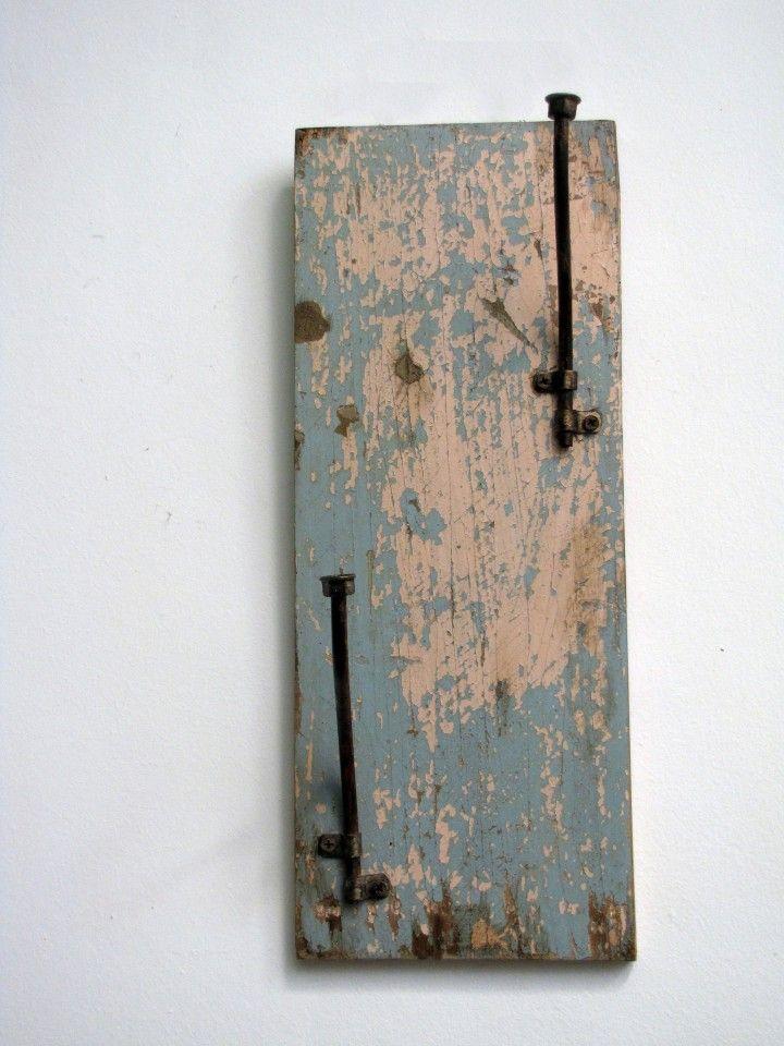 Perchero vertical, realizado con madera de una antigua puerta y partes de un soporte de hierro para macetas. Medidas: 50x20 cm.
