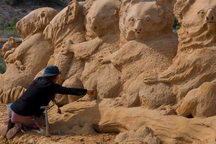 Sculptor Meg Murray finishes a wall of koalas.