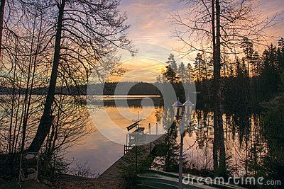 Beautiful summer evening sunset. Pink, orange sky, clouds, trees and forest are reflected in the still water of the lake. On the shore you can see a piece of pier, a beach and a bench for rest.