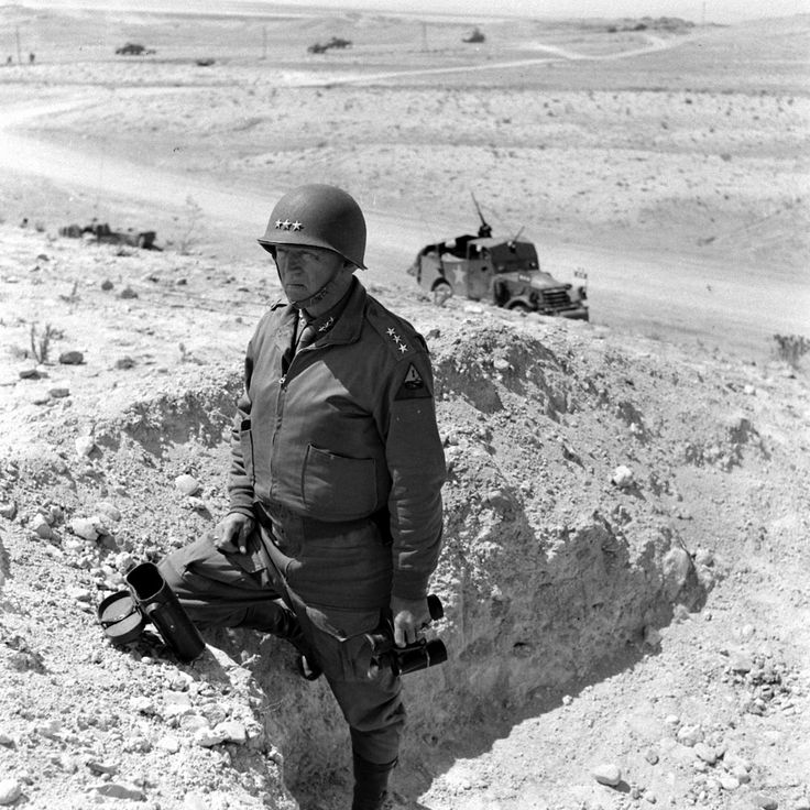 """Gen George S. Patton Jr, commanding 2nd US Army Corps in North Africa, makes a stopover to observe enemy positions. As usual, he is impeccably dressed with field jacket and breeches and uses a spotless pair of field glasses. Patton was always of the mind that being in a war did not negate the need for a soldier """"to look like a soldier"""" although he did make a silent exception for front line troops."""