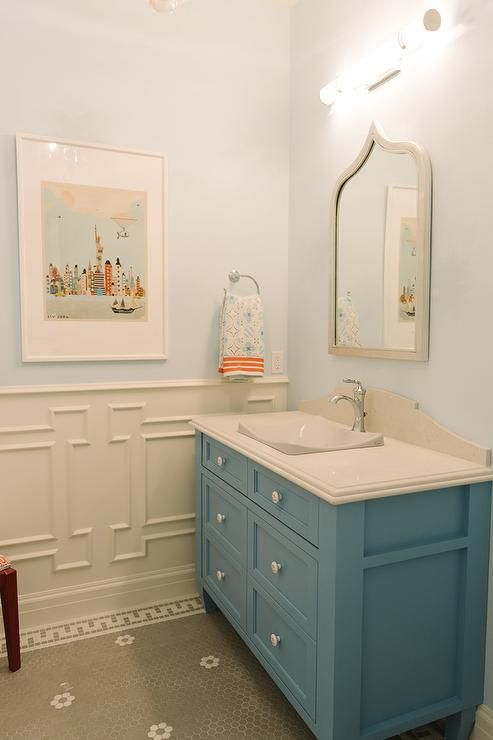 Blue and grey bathroom features upper walls painted sky blue, Benjamin Moore Harbor Fog, and lower walls clad in Greek key wainscoting alongside a gray hex tiled floor accented with white grout.