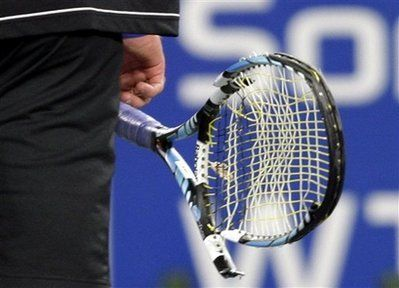 Andy Roddick, of the United States, carries his broken racquet off the court after smashing it against the ground during his quarterfinal match against Spain's Juan Carlos Ferrero, at the China Open tennis tournament in Beijing Friday Sept. 26, 2008. [Agencies]