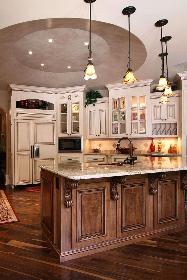 Warm white kitchen cabinets paired with a wood stained ...