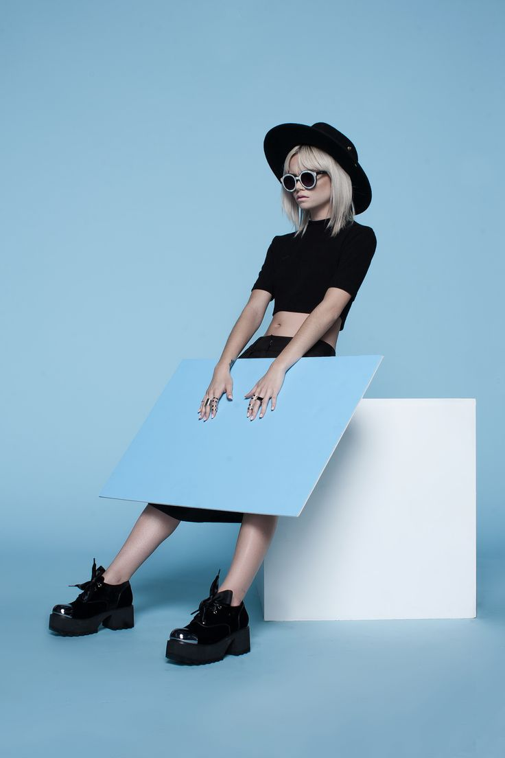 Black platforms, black hat, black crop top, white sunglasses, baby blue background, mod looks. It's Zooji... Check out our selection of platforms and boots on ZOOSHOO and Zooji