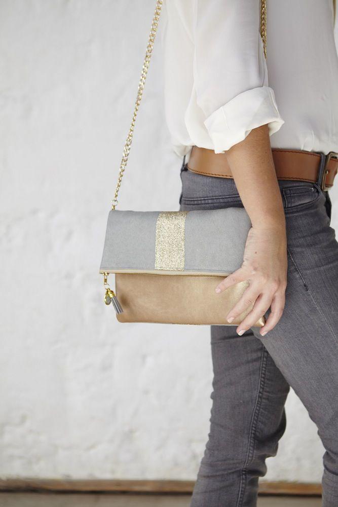 - Sac /Pochette en suédine et simili cuir.- Couleurs : gris vert clair et doré- empiècement tissu à paillettes dorées- Doublure en coton gris- Fermeture éclair YKK beige et dorée- Dimensions : pochette pliée : 25x16 / pochette dépliée : 25x27.- Bicolore et pliable dans les deux sens.- Chaîne amovible de 1m.- Médaillon Madame Zouzou- Pompon gris- Sac entièrement fait à la main à Paris   Expédition sous 7 jours ouvrés.(Pour des commandes Ho...