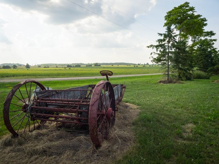 Old farm equipment on a local farm's yard at sunset. #Arthur #Ontario #Antique #lawnart #country #dirtroad