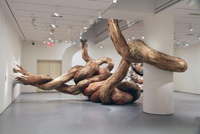 tree trunks burst through gallery walls in henrique oliveira's fantastic installations