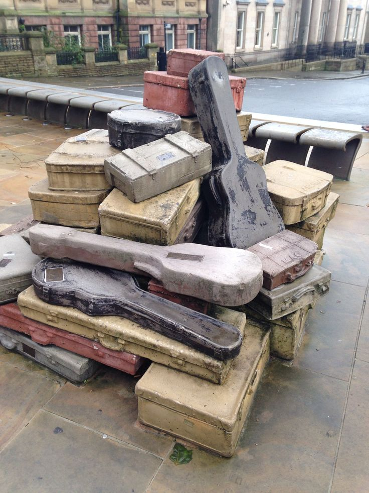 "Liverpool - ""A Case History"" by John King, 1998. Various items of luggage, cast in concrete, are stacked on the pavement -- the labels on the suitcases refer to notable individuals and institutions linked with the local area."