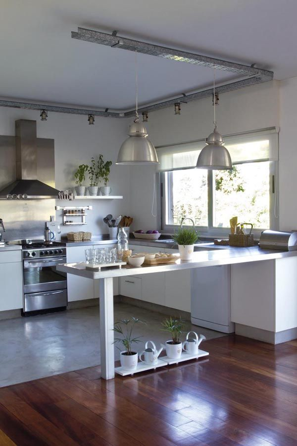 A tono, la cocina usa muebles y estantes en madera laqueada, y una mesada que…