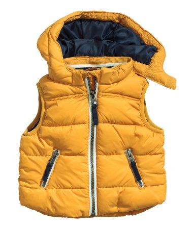 Padded, fleece-lined vest with a detachable lined hood. Zip at front and side pockets with zip.