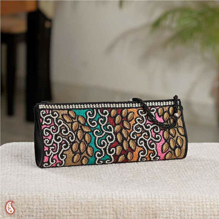 Aapno Rajasthan Multi Coloured Hand Bag  Dazzle everyone with this multi colour clutch with hand embroidered leaves in wheat brown and contrasted with white bead work . Comes with a beaded strap to hang from your wrist or arm. These kind of clutches are latest in trend and goes well with your party attire. #Jewellery #earrings #bangles #necklace #wedding #gifts #surprise #birthday #Indian