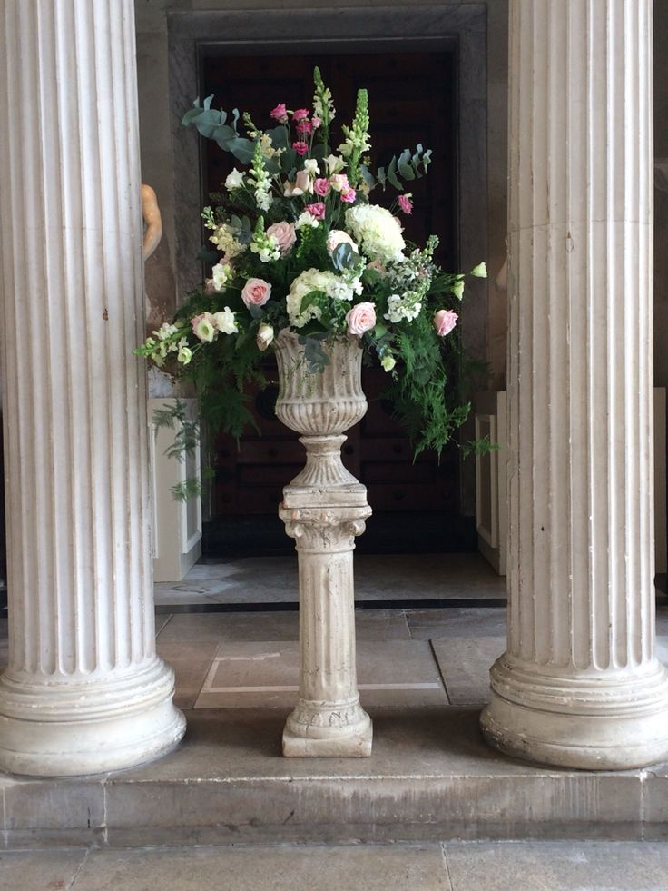 Stone urn display at Woburn sculpture gallery with roses, hydrangea, lisianthus and freesia.