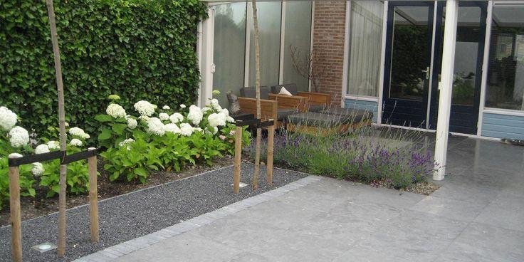 Kleine moderne achtertuin met grijs en wittinten.