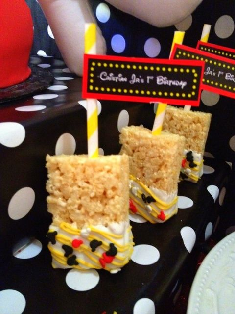 Decorated Rice Krispie Treats at a Mickey Mouse Party. Use cocoa krispies, dip in red candy coating & add yellow candy buttons. Stick a crazy straw in for the handle.