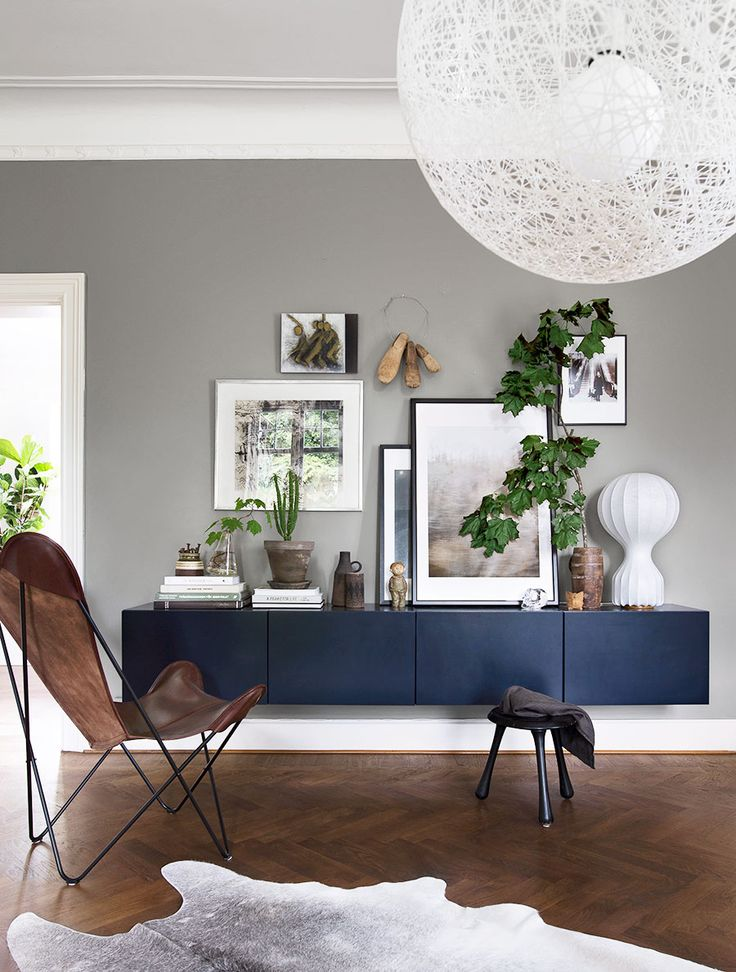 light grey wall, dark sideboard, herringbone floor and leather butterfly chair. Daniella Witte's living room