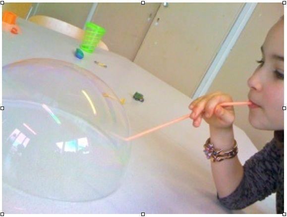 Zeepbellen blazen op tafel met ecologisch afwasmiddel. Klein beetje sop en water in een beker, tafel nat maken met sop en de juiste blaas techniek gebruiken: niet te hard en niet te zacht blazen. Er kunnen ook plasticspeeltjes in. Of heel veel bellen in en aan elkaar.
