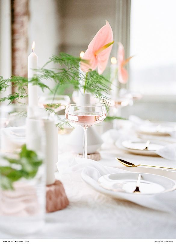 Pink and green table setting with gold cutlery, pink drinks and whote linen