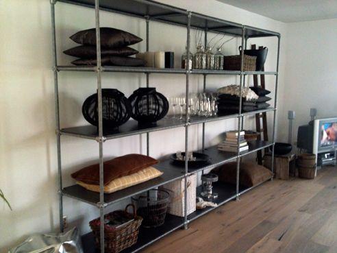 Van steigerbuizen hebben we een originele kast voor in de woonkamer gemaakt. Het lijkt een beetje op een winkelschap. We hebben verbindingsstukken besteld en de steigerbuizen op maat geslepen. Voor de planken hebben we eenvoudig hout van de bouwmarkt gebruikt. Met leuke accessoires heb ik het helemaal afgemaakt.