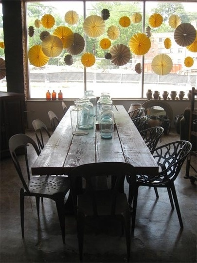 Love the rustic table with mismatched chairs, mason jars, and sunny decorations!