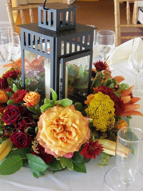 Fun fall lantern arrangement of reds and oranges | Pod Shop Flowers Wedding Designs | #fall #wedding #lantern #centerpiece