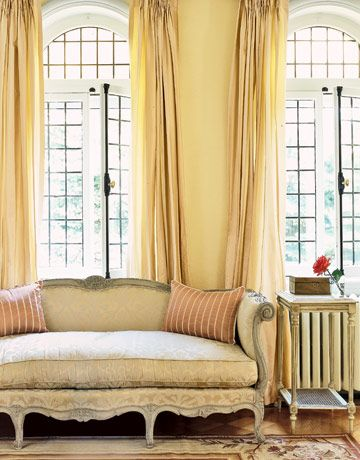 In the living room, champagne-colored taffeta draperies frame leaded windows, in front of which sit an early-18th-century French settee and a marble-topped end table.
